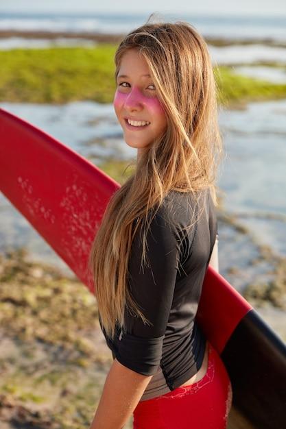 Koncepcja Raju Surfingowego. Dość Młoda Surferka Z Długimi Prostymi Włosami, Nosi Deskę Surfingową, Na Twarzy Ma Odporny Na Słońce Krem Cynkowy Darmowe Zdjęcia