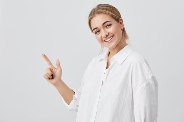 Koncepcja Reklamy. Szczęśliwa Młoda Kobieta Z Blond Włosami Na Sobie Ubranie, Stojąc Z Miejsca Kopiowania Dla Informacji Lub Treści Promocyjnych Darmowe Zdjęcia