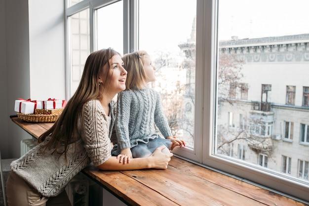 Koncepcja Rodziny. Matka I Córka Patrzeje W Okno. Premium Zdjęcia
