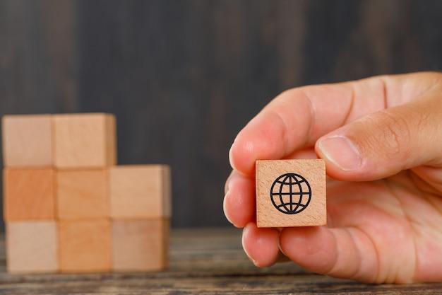 Koncepcja Rodziny Na Widok Z Boku Drewniany Stół. Ręka Trzyma Drewniane Kostki Z Ikonami. Darmowe Zdjęcia