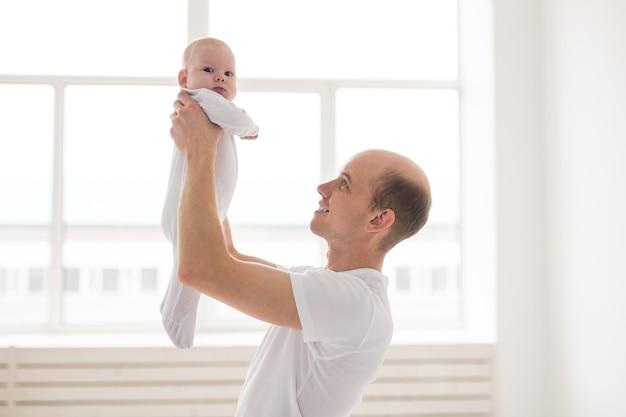 Koncepcja Rodziny, Ojcostwa I Dzieci. łysy Ojciec Trzyma W Domu Uroczego Noworodka Premium Zdjęcia