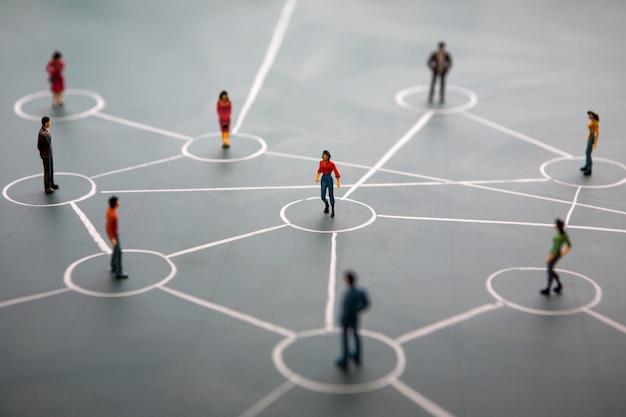 Koncepcja sieci społecznościowej: połączone miniaturowe ludzi na zielonej tablicy Premium Zdjęcia