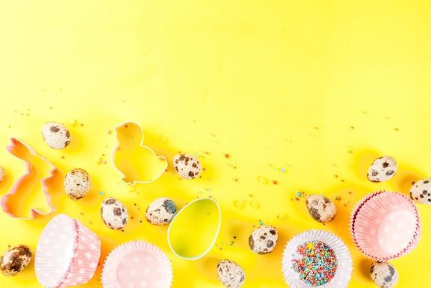 Koncepcja słodkiego pieczenia na wielkanocnym tle gotowania z pieczeniem - z trzepaczką do ubijania wałków do ciastek jajka przepiórcze posypanie cukrem Premium Zdjęcia