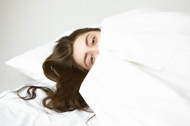 Koncepcja Snu, Odpoczynku I Relaksu. Figlarnie Atrakcyjna Młoda Kobieta O Pięknych Oczach I Ciemnych Włosach, Relaksując Się Na Białej Poduszce, Chowając Się Za Kocem, Patrząc Z Radością Darmowe Zdjęcia