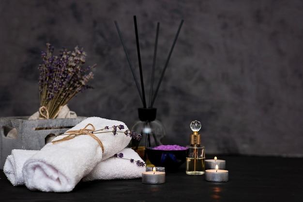Koncepcja Spa. Lawendowa Sól Do Relaksującej Kąpieli, Aromatyczny Olej, świece, Białe Ręczniki, Suche Kwiaty Lawendy, Perfumy Na Szarym Tle. Aromaterapia Premium Zdjęcia