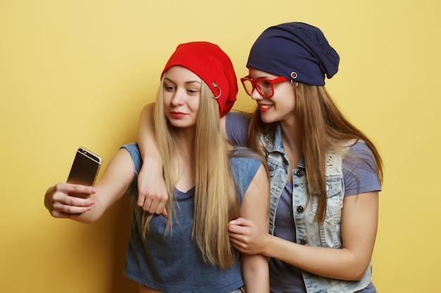 Koncepcja Stylu życia, Emocji, Technologii I Ludzi: Dwie Młode Dziewczyny Hipster Przyjaciółki Biorąc Selfie Na żółto Premium Zdjęcia