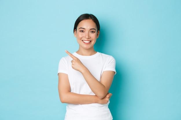 Koncepcja Stylu życia, Piękna I Zakupów. Piękna Szczęśliwa Azjatycka Dziewczyna Z Optymistycznym, Pewnym Siebie Uśmiechem, Wskazująca Lewy Górny Róg, Aby Pokazać Reklamę, Składa Ofertę Promocyjną Na Niebieskiej ścianie Premium Zdjęcia