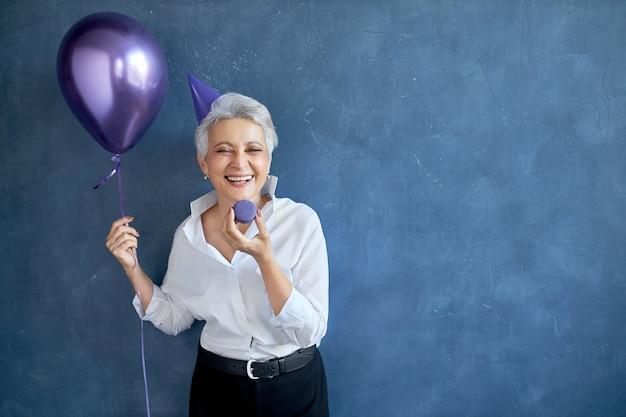 Koncepcja Szczęścia, Radości, Wypoczynku, Zabawy I Rozrywki. Portret Pięknej Beztroskiej Kobiety Na Emeryturze Z Siwymi Włosami Korzystających Z Przyjęcia Urodzinowego Darmowe Zdjęcia
