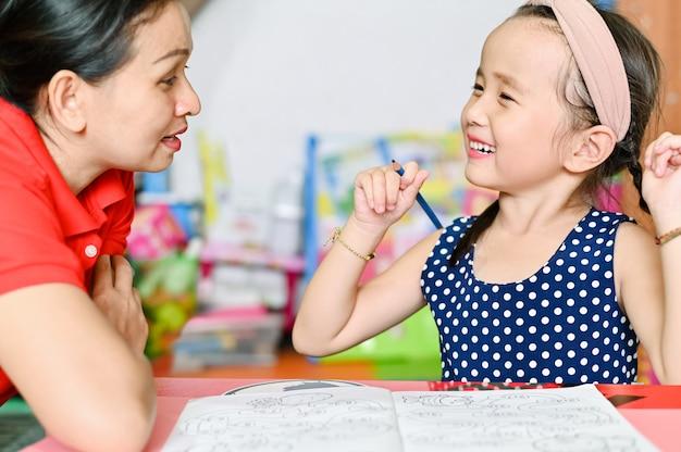 Koncepcja Szkoły Domowej, Azjatyckie Dzieci I Matka Uczą Odrabiania Lekcji W Szkole Premium Zdjęcia