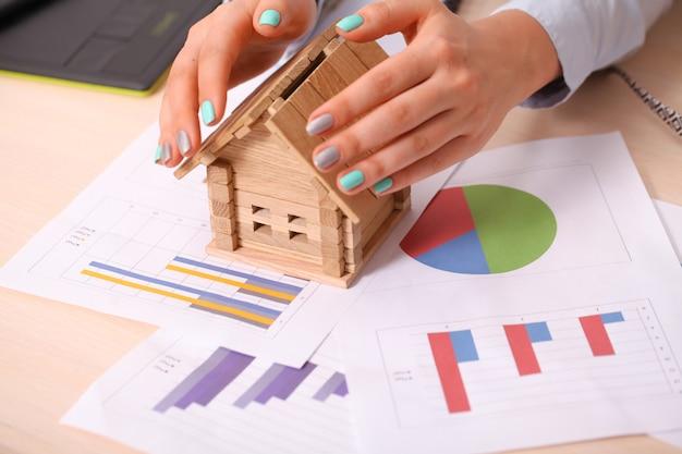 Koncepcja ubezpieczenia i ochrony domu. piękny dom pod rękami kobiety Premium Zdjęcia
