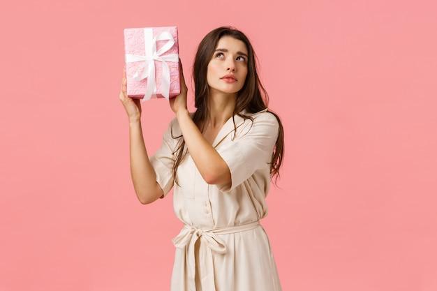 Koncepcja Uroczystości, Kobiety I Oczekiwania. Powabna Ciekawa Młoda Kobieta Drżąca Pudełko Z Zainteresowaniem, Skupiona, Zaintrygowana Tym, Co W środku, Stojąca Różowa ściana, Otrzyma Prezent Premium Zdjęcia