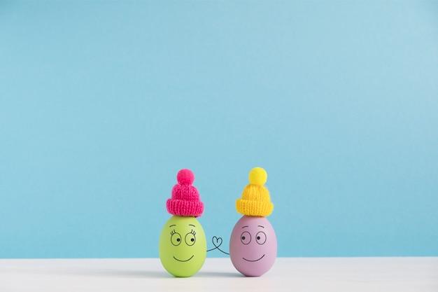 Koncepcja Wakacji Wielkanocnych Z Słodkie Jajka Z Zabawnymi Twarzami. Różne Emocje I Uczucia. Urocza Para W Kapeluszach, Trzymając Się Za Ręce. Premium Zdjęcia