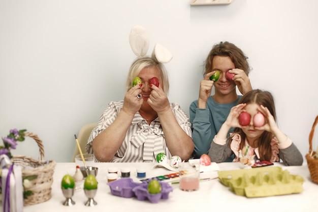 Koncepcja Wielkanocna. Mała Dziewczynka Z Bratem I Babcią Kolorowanki Jajka Na Wielkanoc. Darmowe Zdjęcia