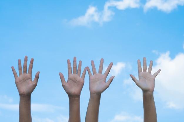 Koncepcja wolontariatu. ręki ludzie z niebieskim niebem na tle Premium Zdjęcia