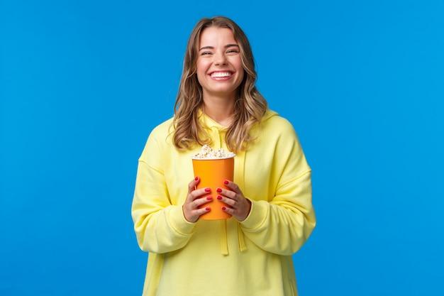 Koncepcja Wypoczynku, Zabawy I Młodzieży. Przyjazna Szczęśliwa Blond Europejka, Ciesząca Się Weekendami, Jedząca Popcorn I Oglądająca Komedie, Odwiedza Kino, Aby Zobaczyć Nowy Film, Stać Premium Zdjęcia
