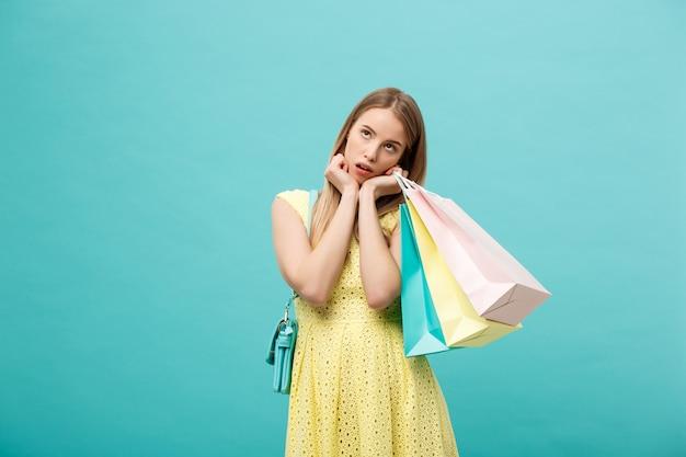 Koncepcja Zakupów I Sprzedaży: Piękna Nieszczęśliwa Młoda Kobieta W żółtej Eleganckiej Sukni Z Torbą Na Zakupy. Premium Zdjęcia