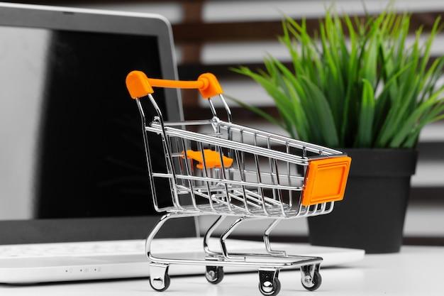 Koncepcja Zakupów Online. Wózek Na Zakupy, Laptop Na Biurku Premium Zdjęcia