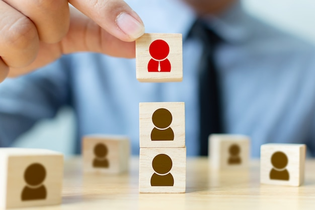 Koncepcja zarządzania zasobami ludzkimi i rekrutacji buduje zespół. biznesmen ręka stawia drewnianego sześcianu blok na wierzchołku Premium Zdjęcia