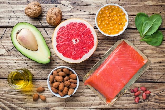 Koncepcja Zdrowe Produkty Przeciwutleniacze żywności: Ryby I Awokado, Orzechy I Olej Z Ryb, Grejpfruty Na Drewnianym Tle. Premium Zdjęcia