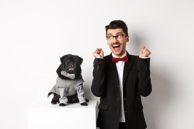 Koncepcja Zwierząt, Strony I Uroczystości. Wesoły Właściciel Psa W Garniturze Stojący W Pobliżu ślicznego Czarnego Mopsa W Kostiumie, Cieszący Się I świętujący Zwycięstwo, Stojący Nad Białym. Premium Zdjęcia