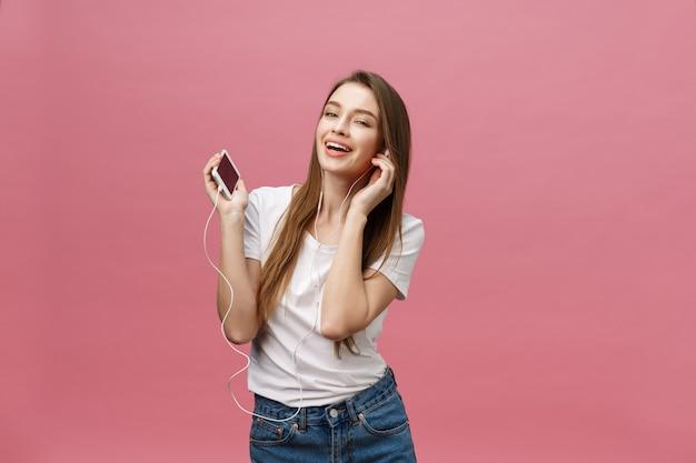 Koncepcja życia. młoda kobieta używa telefon dla słuchać muzyka na różowym tle Premium Zdjęcia