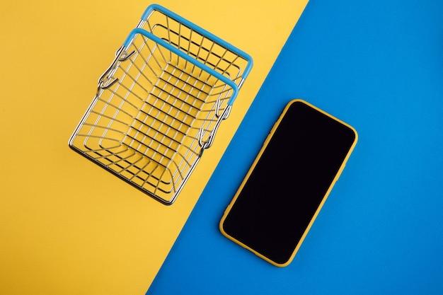 Koncepcje Zakupów Online Z Koszykiem I Smartfonem Na żółtym Czerwonym Tle. Rynek E-commerce. Logistyka Transportu. Handel Detaliczny. Premium Zdjęcia