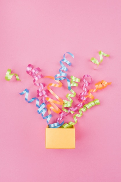 Konfetti wyskakujące z pudełka z różowym tłem Darmowe Zdjęcia