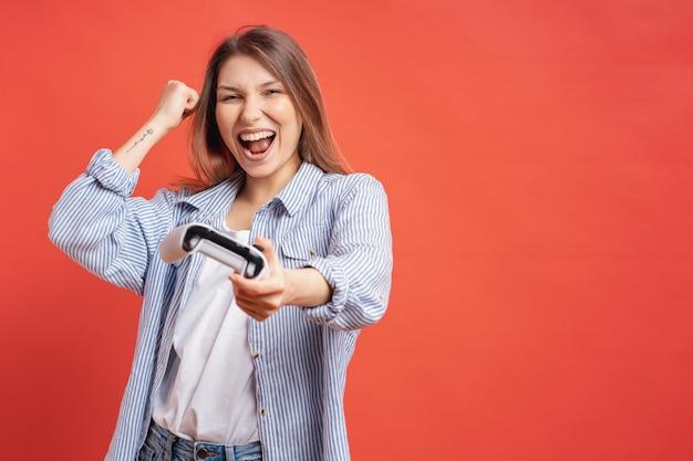 Konkurencyjna Dziewczyna świętuje Wygraną Trzymając Kontroler Joysticka Na Czerwonej ścianie. Darmowe Zdjęcia