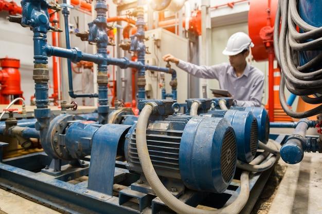 Konserwacja azjatyckiego inżyniera sprawdzanie danych technicznych wyposażenia systemu skraplacz pompa wodna i manometr, pompa wodna. Premium Zdjęcia