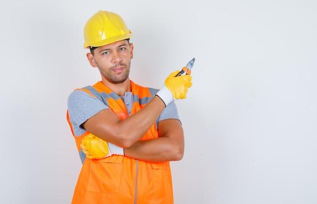 Konstruktor Mężczyzna W Mundurze, Kasku, Rękawiczkach Trzymających Szczypce, Widok Z Przodu. Darmowe Zdjęcia
