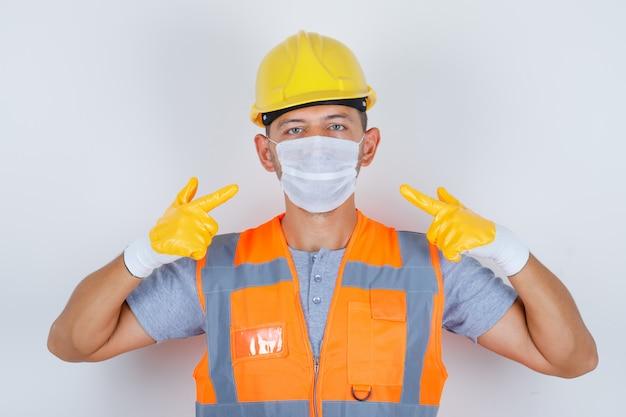 Konstruktor Mężczyzna Wskazując Jego Maskę Medyczną W Mundurze, Hełmie, Rękawiczkach, Widok Z Przodu Darmowe Zdjęcia