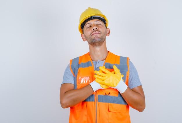Konstruktor Trzymający Ręce Na Sercu W Mundurze, Kasku, Rękawiczkach I Patrząc Wdzięczny, Widok Z Przodu Darmowe Zdjęcia