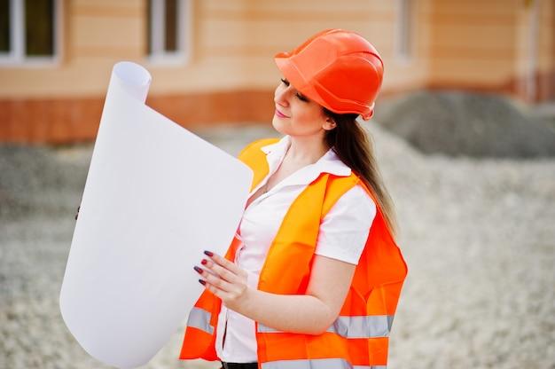Konstruuje budowniczej kobiety w jednolitej kamizelce i pomarańczowym hełmie ochronnym trzyma biznesowego papier przeciw nowemu budynkowi Premium Zdjęcia