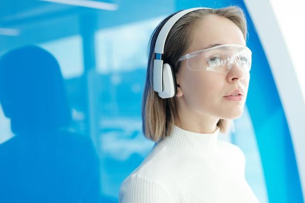 Kontemplacyjna Atrakcyjna Dziewczyna W Bezprzewodowych Słuchawkach I Nowatorskich Goglach Pracujących W Nowoczesnym Biurze Premium Zdjęcia