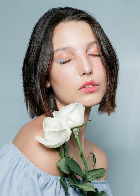Kontemplacyjna kobieta pozuje z różami Darmowe Zdjęcia