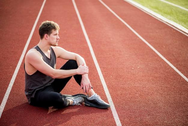 Kontemplował młodego sportowca siedzi na torze wyścigowym Darmowe Zdjęcia