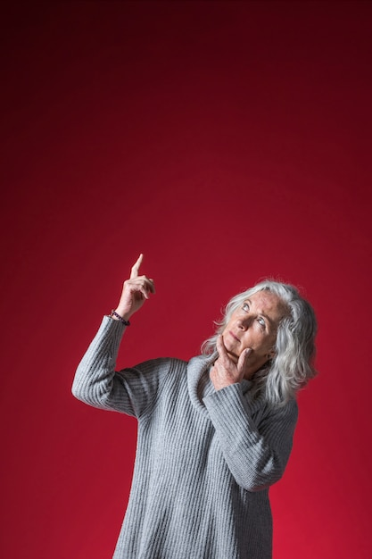 Kontemplująca Starsza Kobieta Wskazuje Palec W Górę Stać Przeciw Czerwonemu Tłu Darmowe Zdjęcia