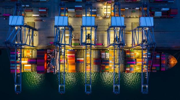 Kontenerowiec pracuje w nocy, biznes import logistyka eksportu i transportu. Premium Zdjęcia
