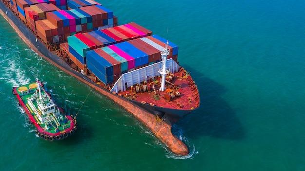 Kontenerowiec przybywający do portu, holownik i kontenerowiec płynący do portu morskiego, logistyczny import eksportowy i transport, widok z lotu ptaka. Premium Zdjęcia