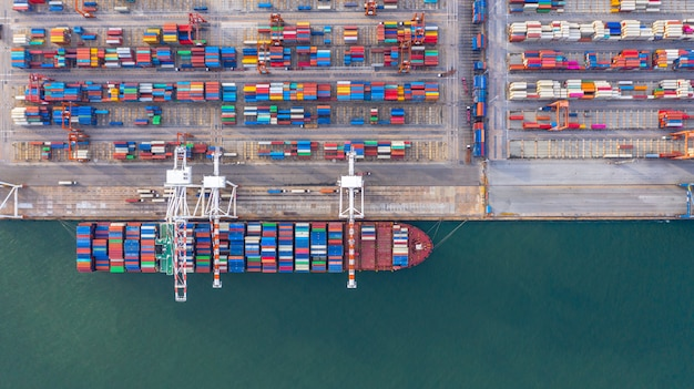 Kontenerowiec załadunek i rozładunek w głębokim porcie morskim, widok z lotu ptaka import i eksport logistyki biznesowej Premium Zdjęcia