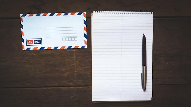 Koperta, długopis, pusty papier na drewnianym stole Premium Zdjęcia