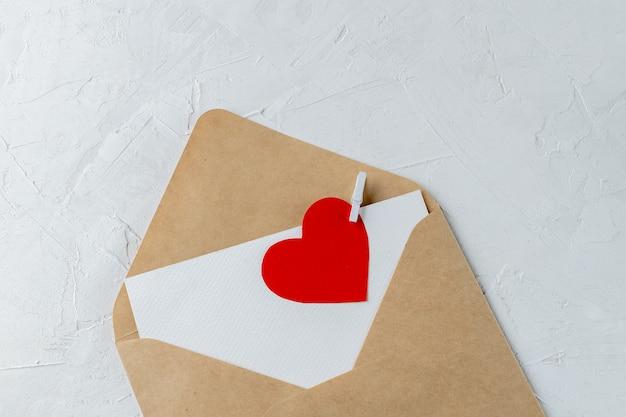 Koperta xraft, pusta notatka miłosna z obciętym czerwonym sercem z papieru Premium Zdjęcia