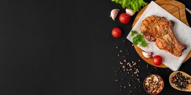 Kopia mięsa z grilla, ciemna powierzchnia, zioła, sałata, pomidor, czarna przyprawa w drewnianych łyżkach Premium Zdjęcia