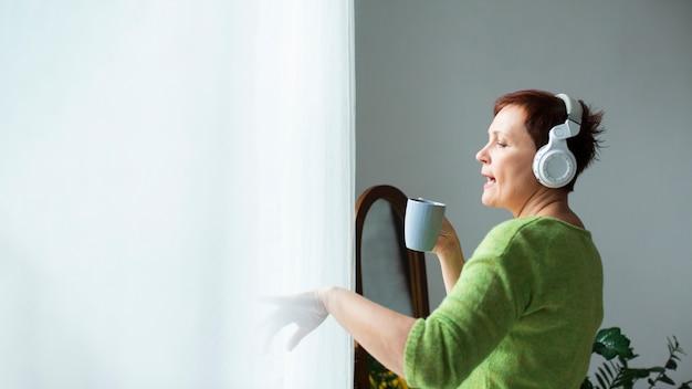 Kopiowanie miejsca starszy kobieta śpiewa w pucharze Darmowe Zdjęcia