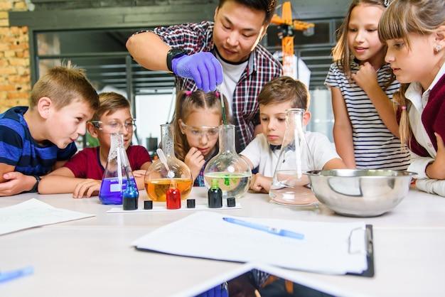 Koreański Naukowiec Pokazuje Uczniom Szkół Podstawowych Eksperymenty Dotyczące Reakcji Chemicznych W Nowoczesnej Klasie Laboratoryjnej. Premium Zdjęcia