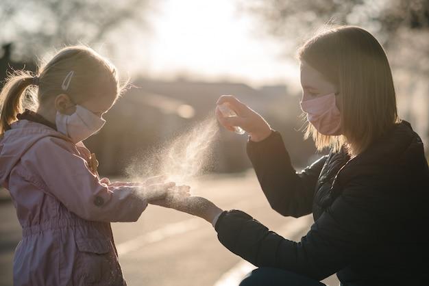 Koronawirus. Kobieta W Masce Ochronnej Używać Dezynfekcji W Sprayu Na Ręce Dziecka Na Ulicy. środki Zapobiegawcze Przeciwko Infekcji Covid-19. Antybakteryjny Spray Do Mycia Rąk. Ochrona Przed Chorobami. Premium Zdjęcia
