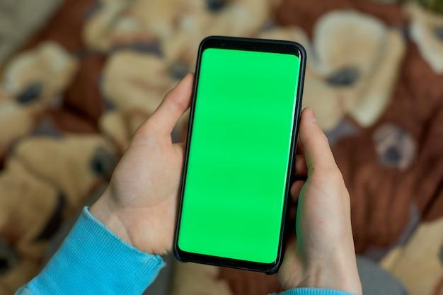 Korzystanie Ze Smartfona Z Zielonym Ekranem. Ręce Przewijanie Stron, Dotykając Ekranu Dotykowego. Widok Z Góry. Kluczowanie Kolorem Premium Zdjęcia