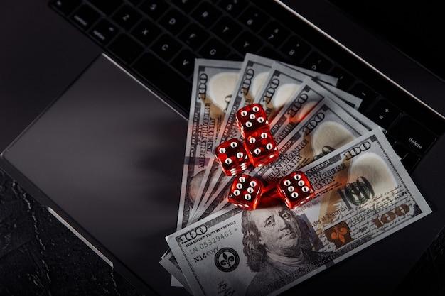 Kości I Banknotów Dolara Na Klawiaturze Laptopa. Koncepcja Kasyna Online I Hazardu Premium Zdjęcia