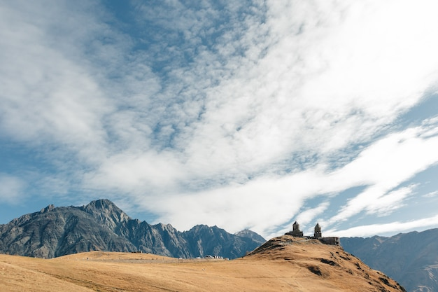 Kościół Trójcy Gergeti Znany Jako Tsminda Sameba Na Tle Grzbietu Górskiego I Chmur, Stepantsminda, Kazbegi, Georgia. Premium Zdjęcia