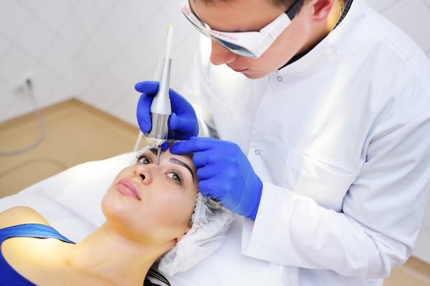 Kosmetyczka Chirurg Usuwa Pigmenty I Siatki Naczyniowe Na Skórze Pacjenta - Piękna Młoda Kobieta Laser Neodymowy Premium Zdjęcia